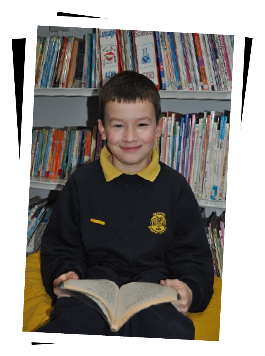 A Delapre child sitting smiling with a book.